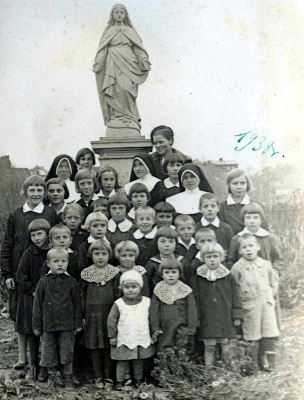 Na prezentowanym przez nas zdjęciu są sieroty wraz z Siostrami Rodziny Maryi przy figurze Matki Boskiej w ogrodzie przy domu na Słowackiego 37. Zdjęcie ostało udostępnione dzięki Muzeum Historyczno-Archeologicznego w Ostrowcu Św.